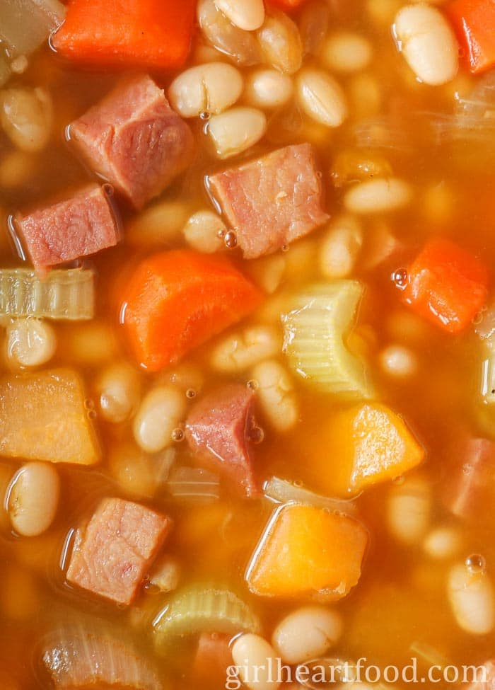 Close-up of boiled beans with ham and vegetables in broth.