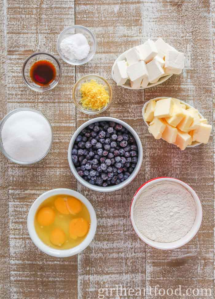 Ingredients for a lemon blueberry cake on a wooden board.