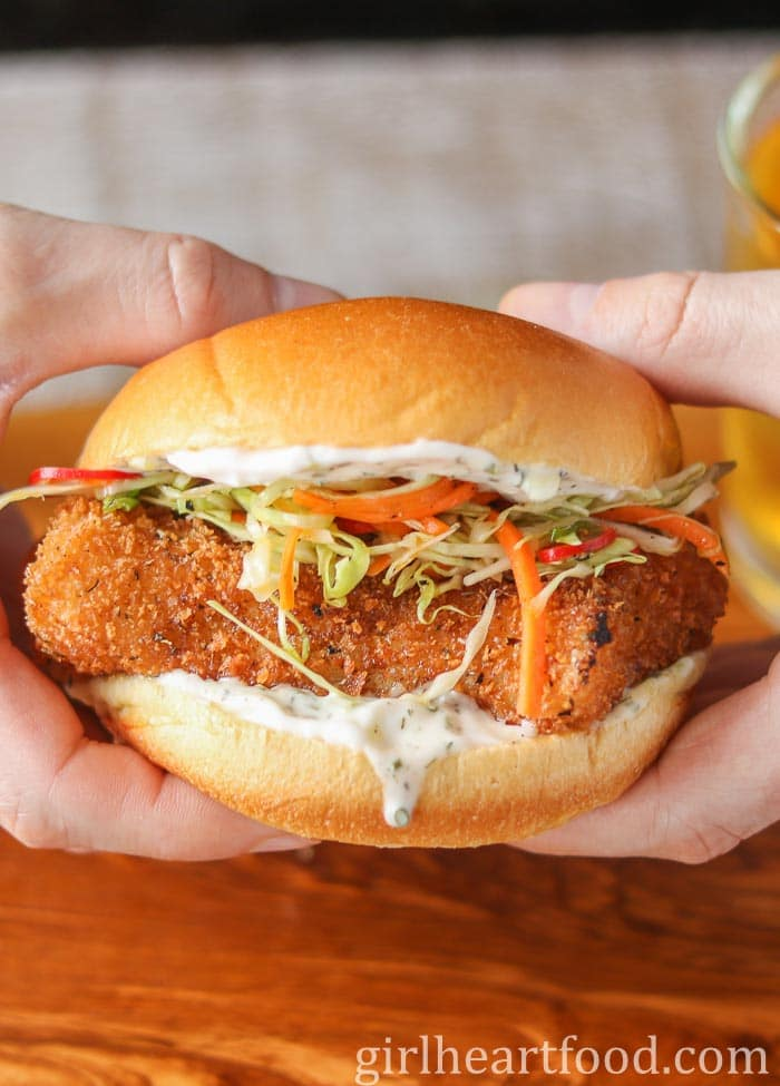 Two hands holding a fried fish burger that has been garnished with tartar sauce and homemade coleslaw.