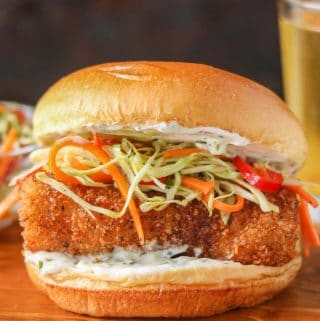 A panko coated fish burger garnished with tartar sauce and coleslaw on a wooden board.