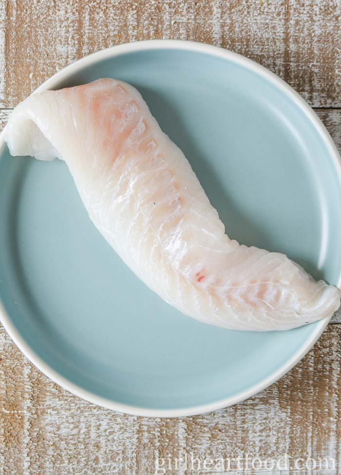 An uncooked cod fillet on a blue plate.