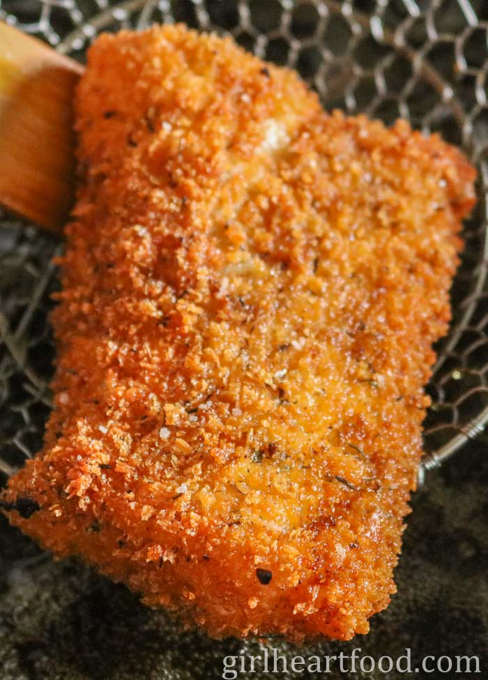 Pulling up a piece of panko fish from oil with a spider strainer.