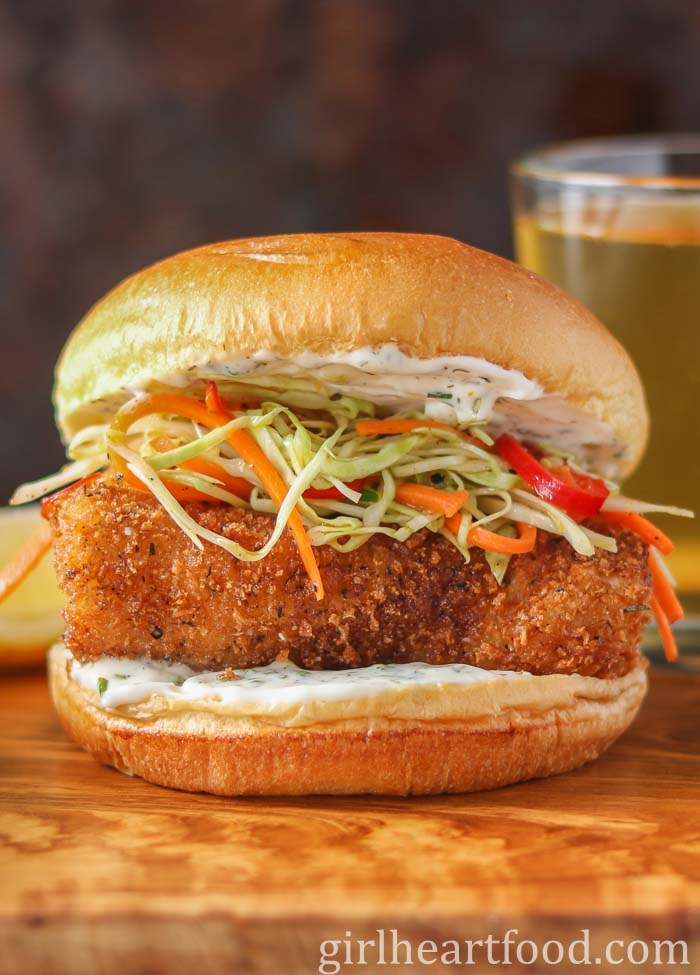 A panko fish burger garnished with coleslaw and homemade tartar sauce on a wooden platter.