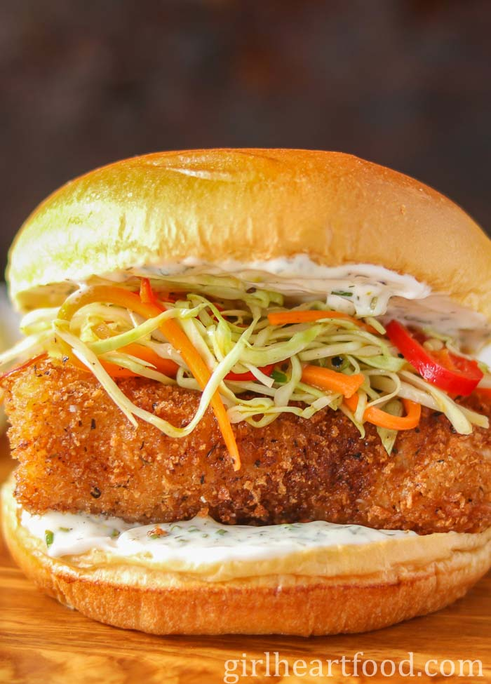 A close-up of a panko fish burger garnished with tartar sauce and coleslaw.