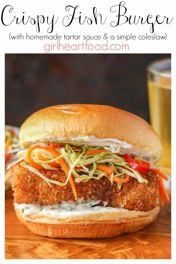 A panko crusted fish burger garnished with tartar sauce and coleslaw on a wooden board.