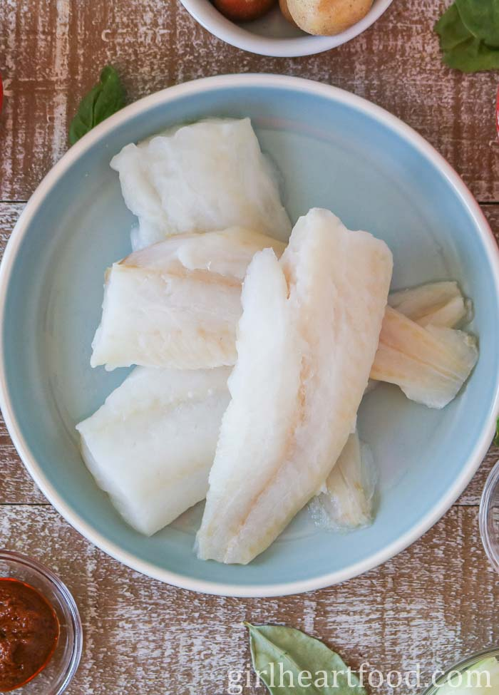 Raw white fish on a blue plate.