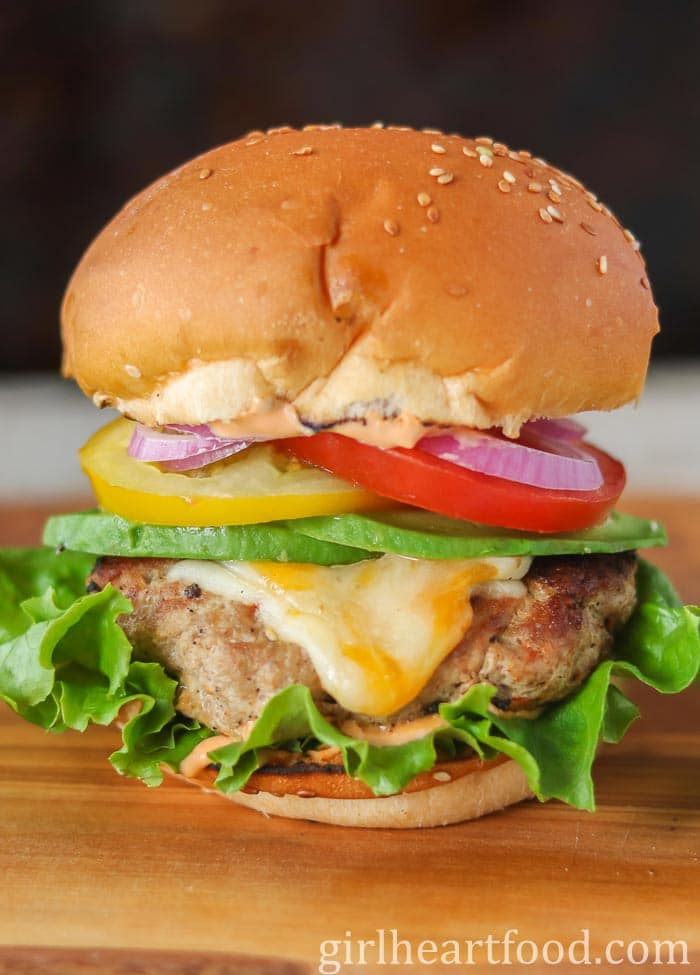A homemade turkey burger with cheese, avocado and veggies on a wooden board.