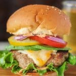 A ground turkey burger stacked high with cheese and veggies on a wooden board.