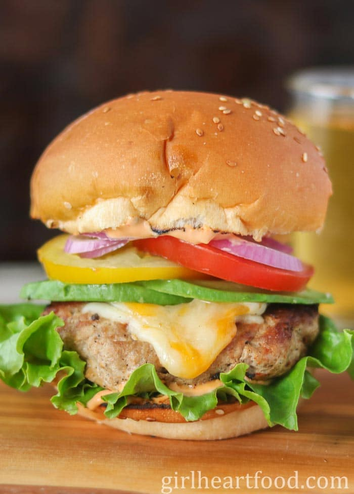 A ground turkey burger stacked high with cheese, veggies, avocado and sauce.