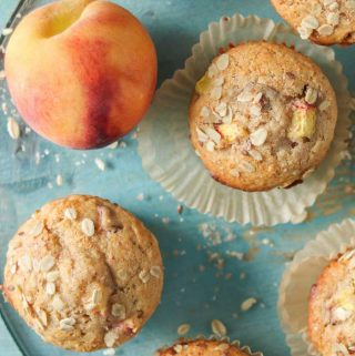Peach muffins on a blue platter next to a fresh peach.