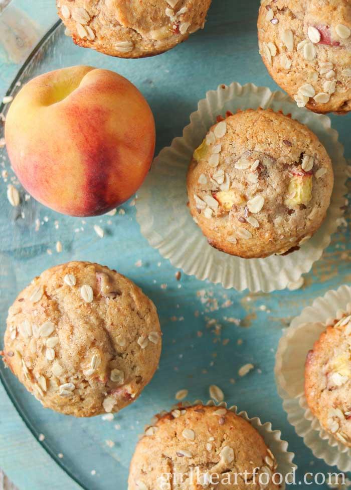 Peach muffins on a blue platter next to a fresh peach.