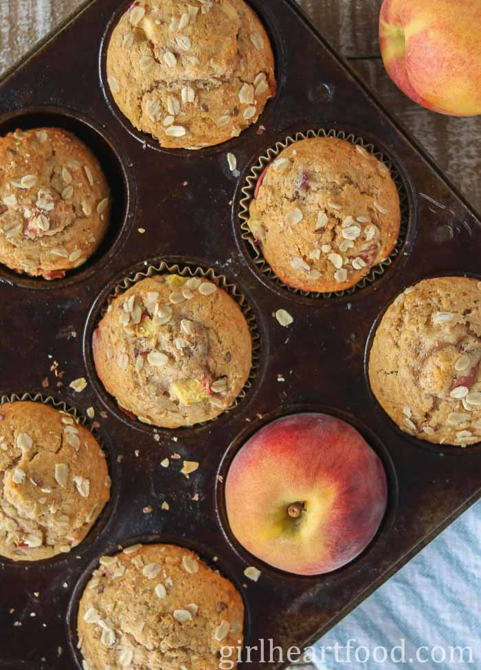 Peach muffins in a muffin pan with a peach in one of the holes.