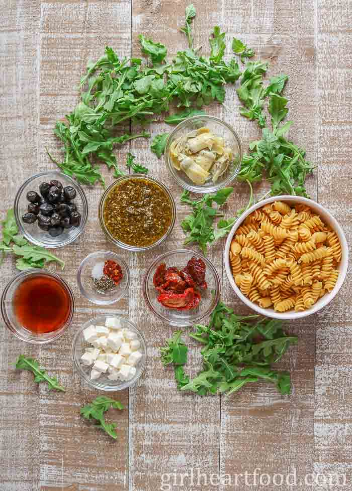 Ingredients for an easy pasta salad recipe on a wooden board.