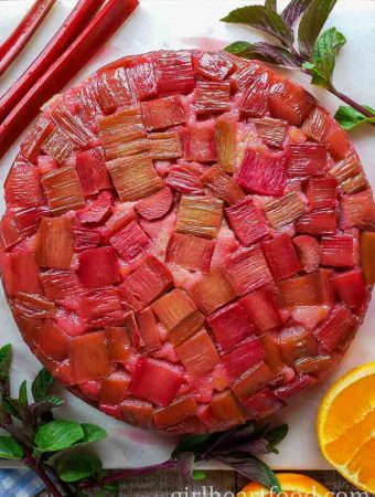 A rhubarb upside-down cake on a white platter alongside mint, orange and rhubarb stalks.