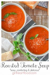Two bowl of roma tomato soup garnished with parmesan and basil.