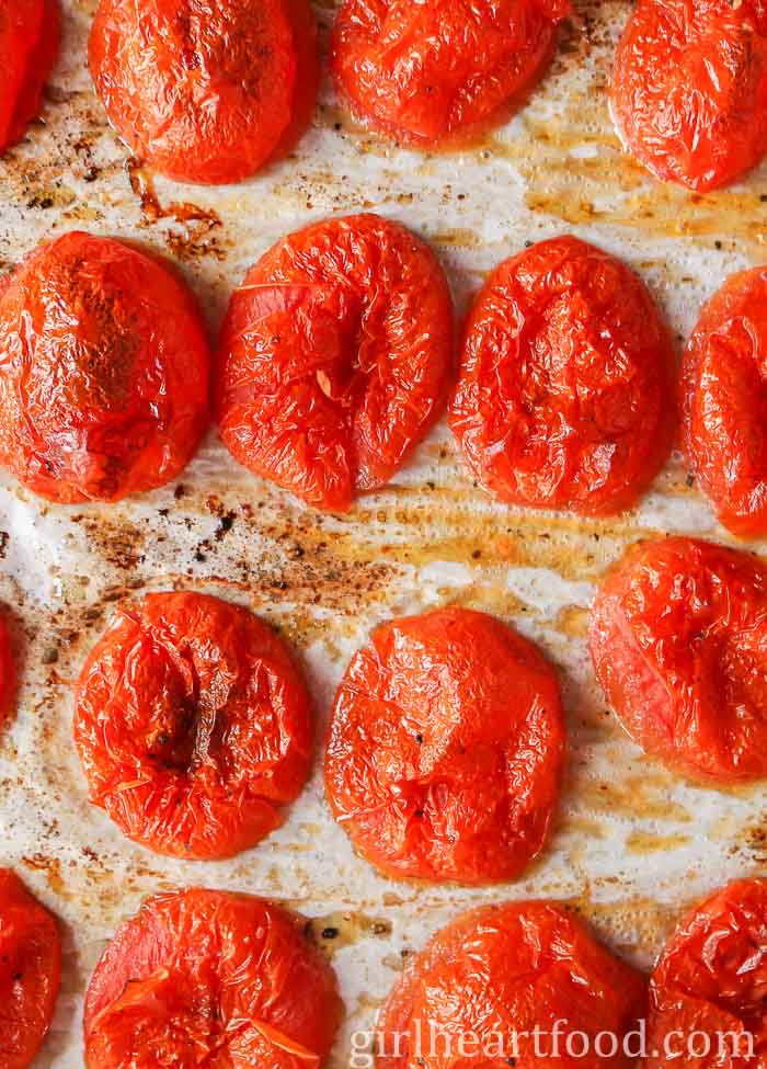 Roasted roma tomatoes on a parchment lined sheet pan.