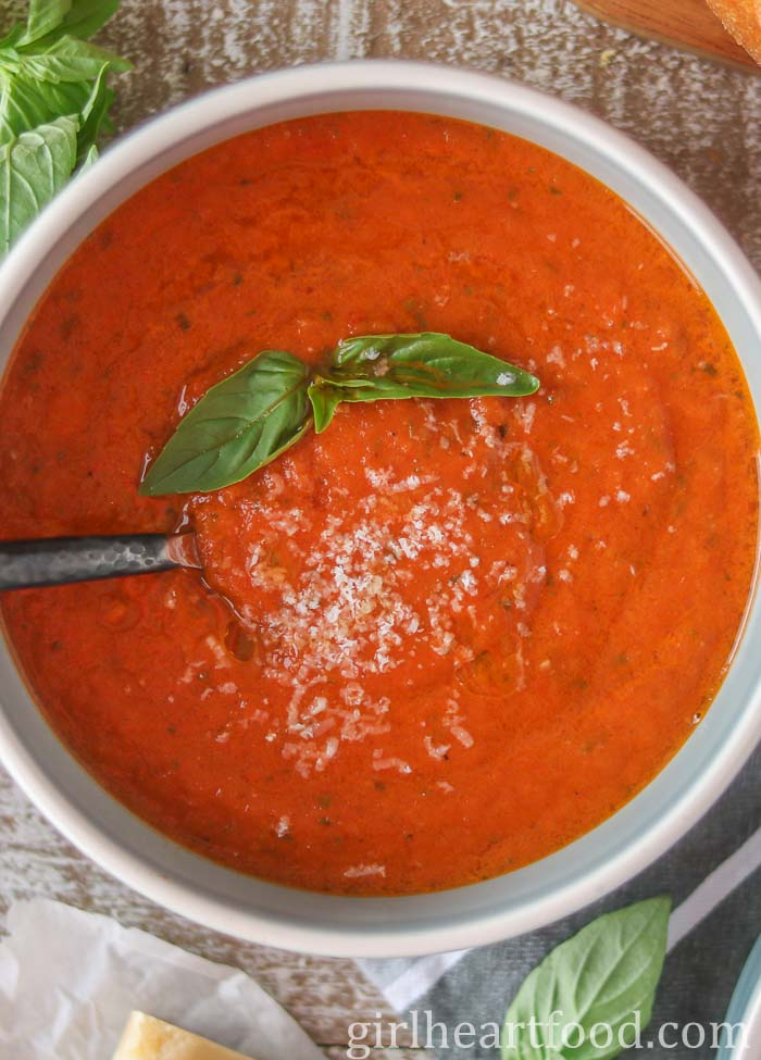 Close-up of a bowl of tomato soup garnished with basil and cheese with a spoon dunked into it.