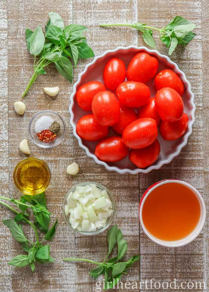 Ingredients for homemade tomato with fresh tomatoes on a wooden board.
