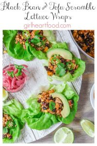 A platter of vegan lettuce wraps made with tofu scramble and black beans next to a dish of pickled red onion.