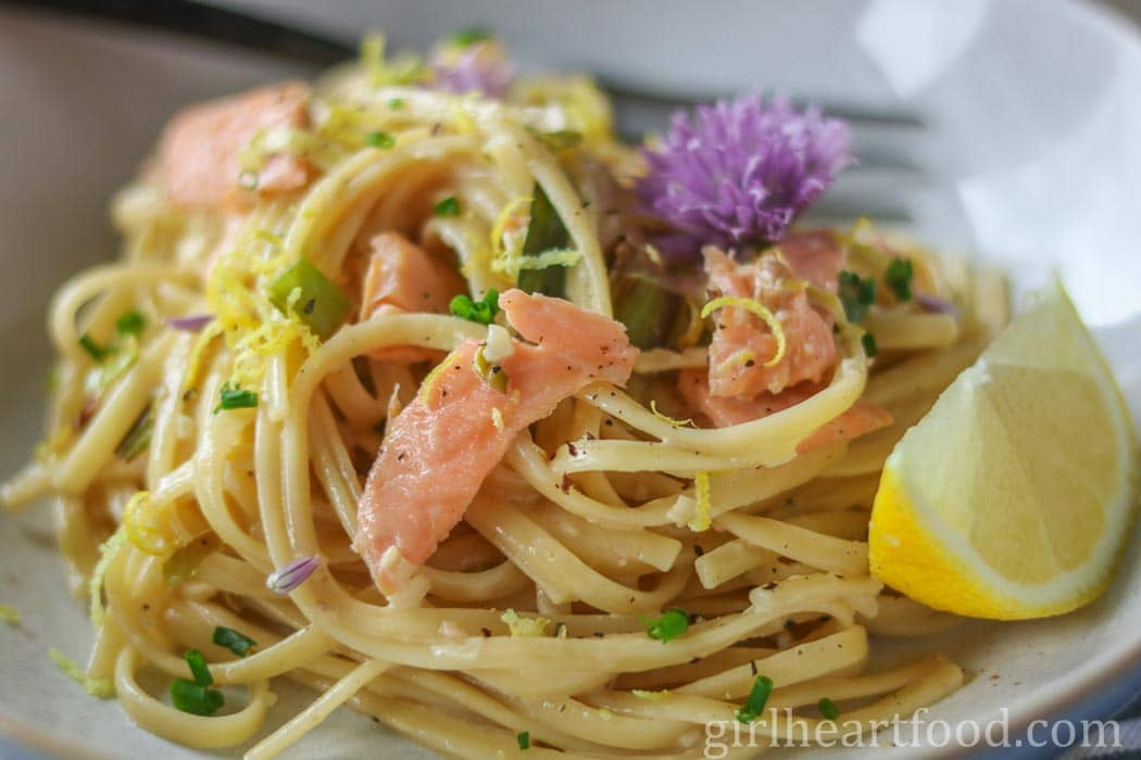 Salmon pasta on a white plate garnished with a chive flower and lemon wedge.