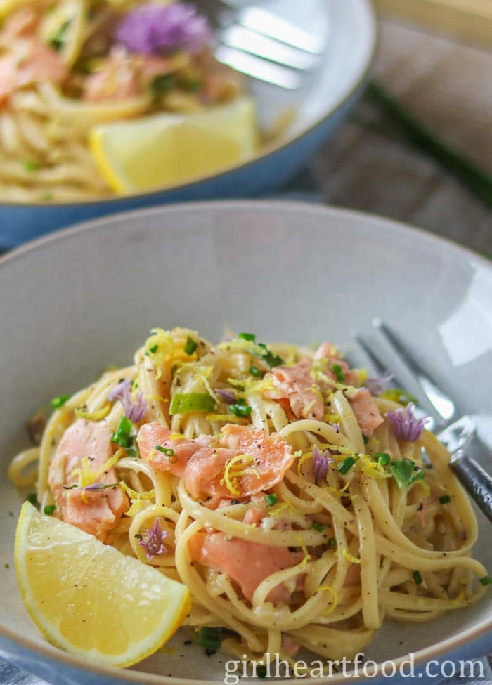 Bowl of pasta with salmon and garnished with lemon and chives.