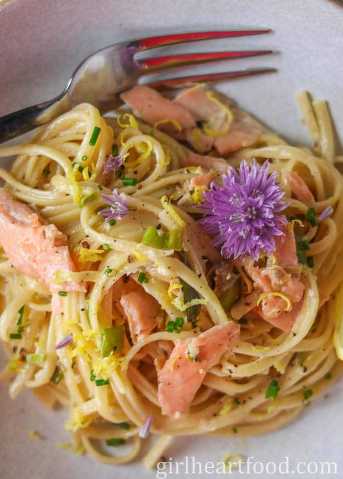 Close up of a plate of creamy smoked salmon pasta garnished with a fresh chive flower.
