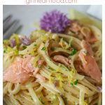 Bowl of creamy smoked salmon pasta garnished lemon, chives and a chive flower.