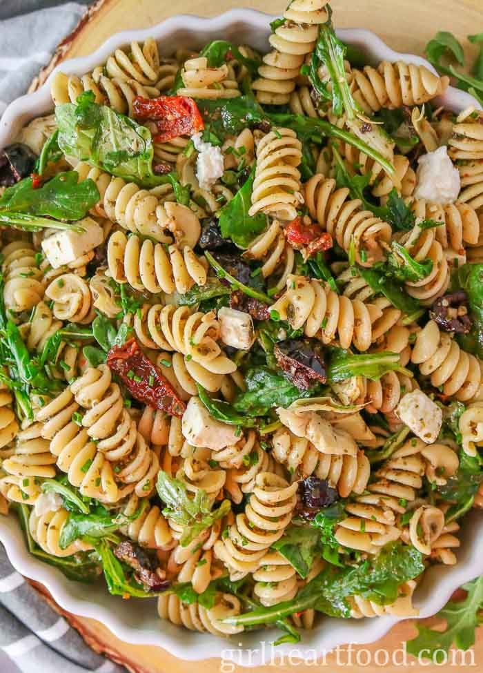 Large white bowl of pasta salad with feta, olives, sun-dried tomatoes, artichokes and arugula.