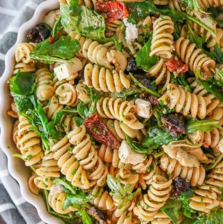 Large white bowl of a pesto pasta salad with arugula.