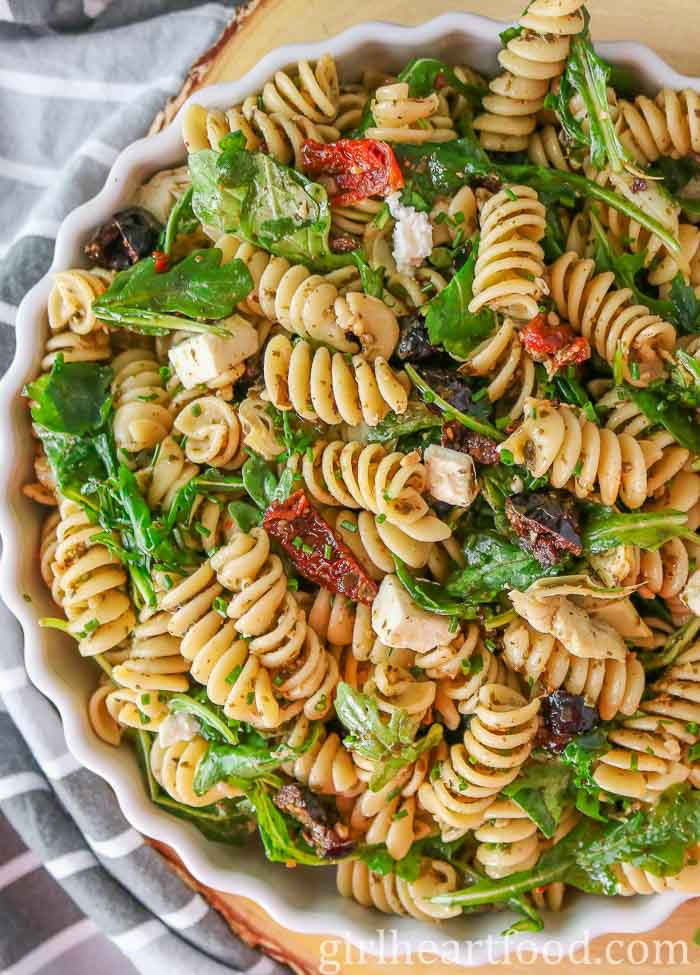 Large white bowl of a pesto pasta salad recipe with feta, arugula, sun-dried tomatoes, artichokes and olives.