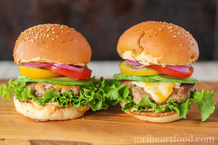 Two ground turkey burgers on a wooden board garnished with cheese, avocado, tomato, onion, lettuce and sauce.