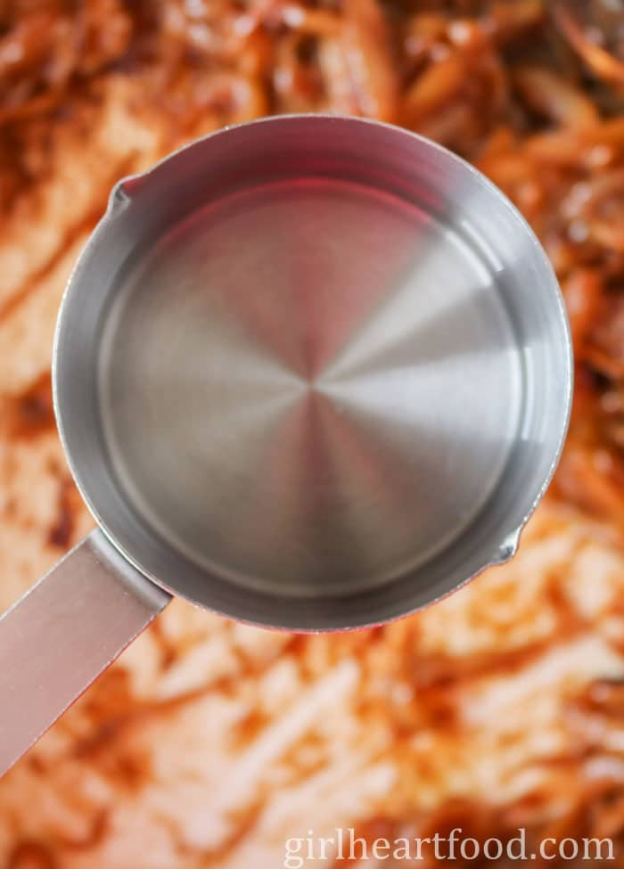 A measuring cup of water about to be poured into a pan of caramelized onions.