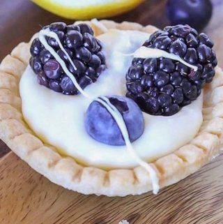 Lemon cream tart with fresh berries and white chocolate drizzle.