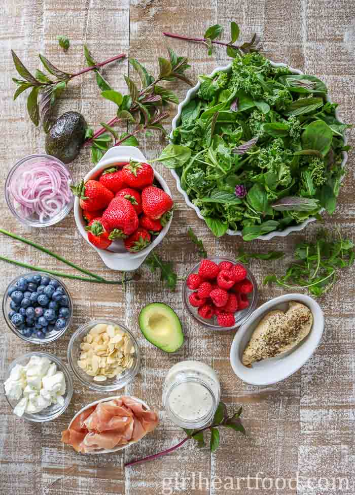 Ingredients for a hearty mixed greens berry salad recipe on a wooden board.
