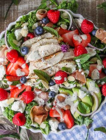 Bowl of green salad with fruit, chicken, prosciutto, toppings and dressing.