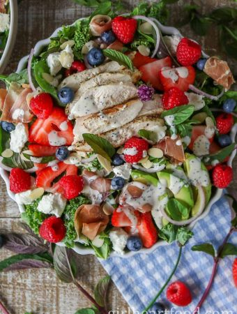 Large bowl of mixed greens berry salad with plenty of greens, berries, chicken, prosciutto, sliced almonds, goat cheese and avocado drizzled with a poppy seed dressing.