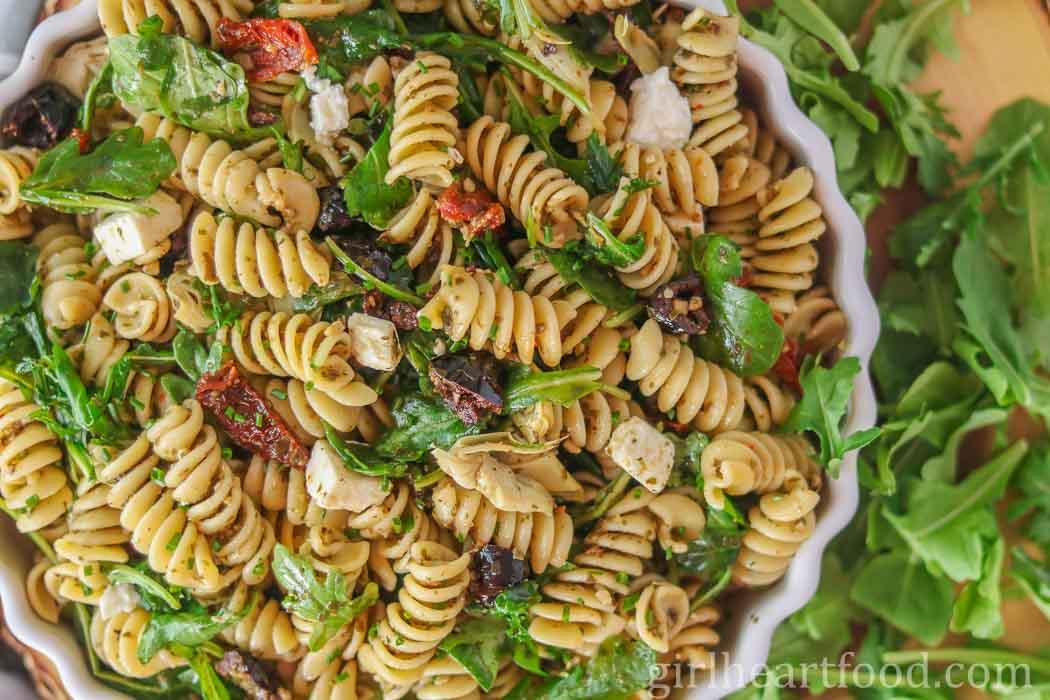 White bowl of Mediterranean pesto pasta salad next to arugula.