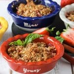 Small dishes of strawberry rhubarb crisp with the front dish garnished with fresh basil.