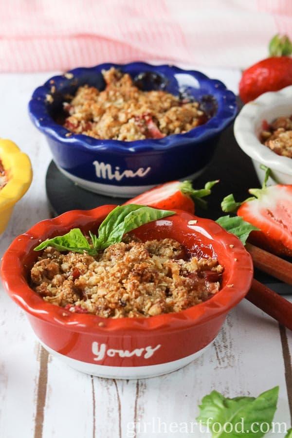 Small dishes of strawberry rhubarb crispy garnished with fresh basil.