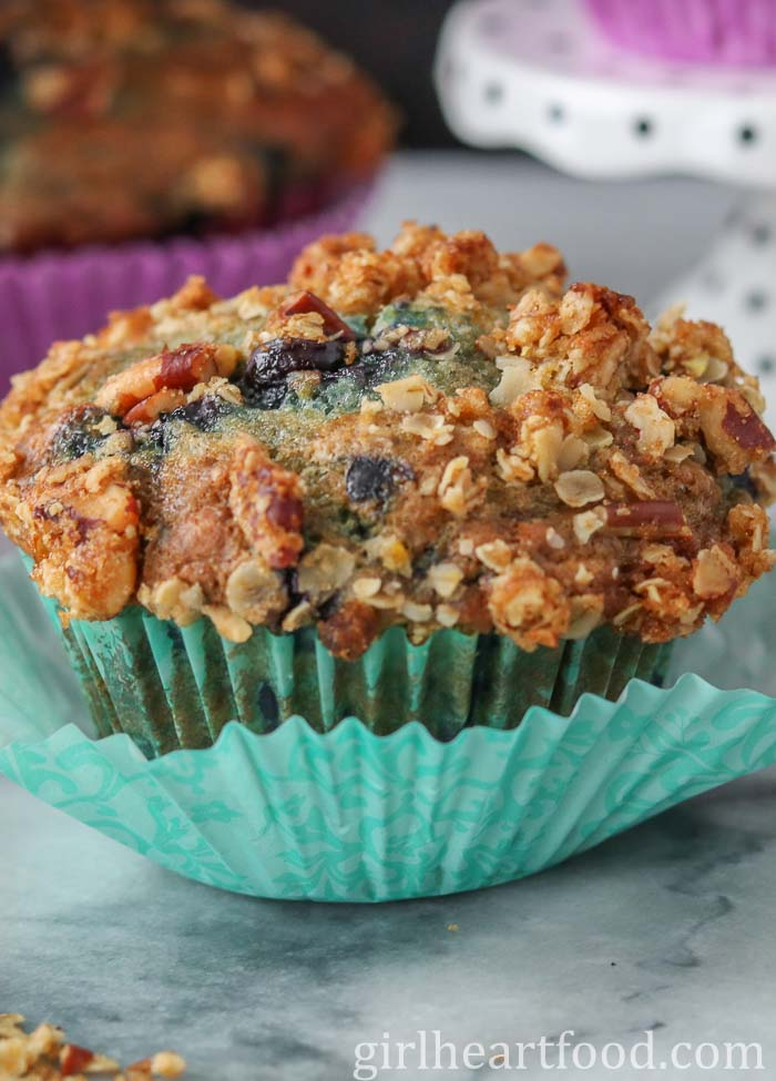 A blueberry muffin made with frozen blueberries wrapped in a teal colour muffin liner.