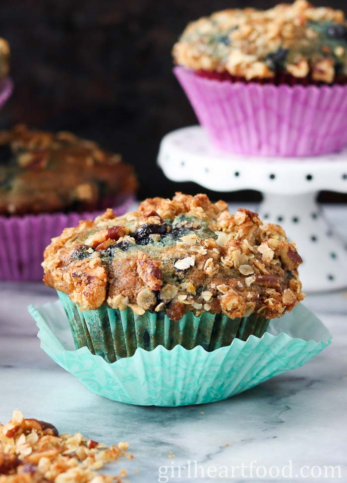 A blueberry muffin with crumble wrapped in a teal muffin liner.