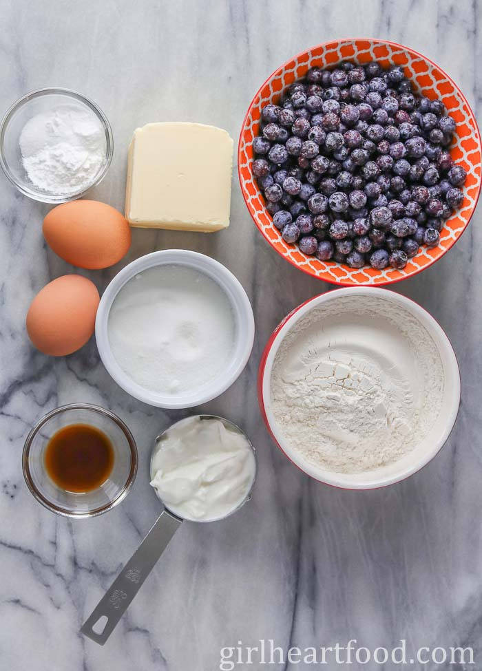 Ingredients for blueberry muffins with frozen blueberries on a wooden board.