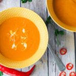 Two bowls of an easy carrot soup with coconut milk alongside chili and cilantro.