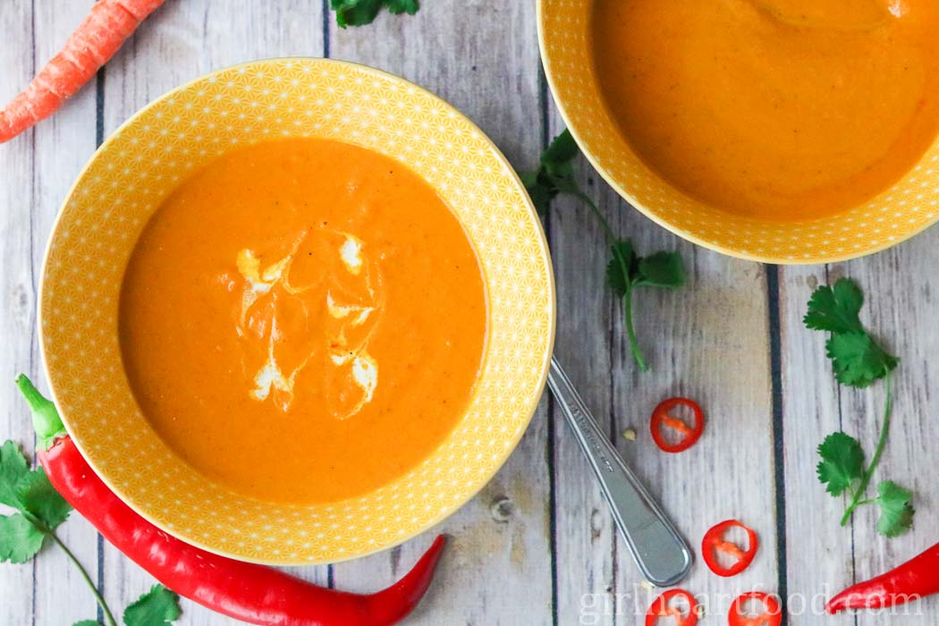 Two bowls of a creamy carrot soup alongside red chili pepper and cilantro.