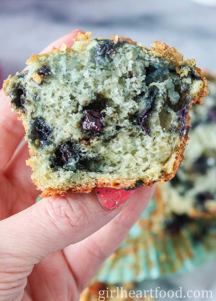 Holding up a moist blueberry muffin that has been cut in half to show interior.