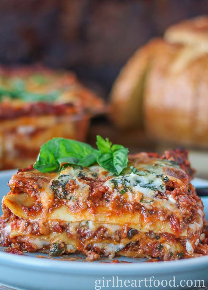 Piece of lasagna with cottage cheese on a blue plate garnished with fresh basil.