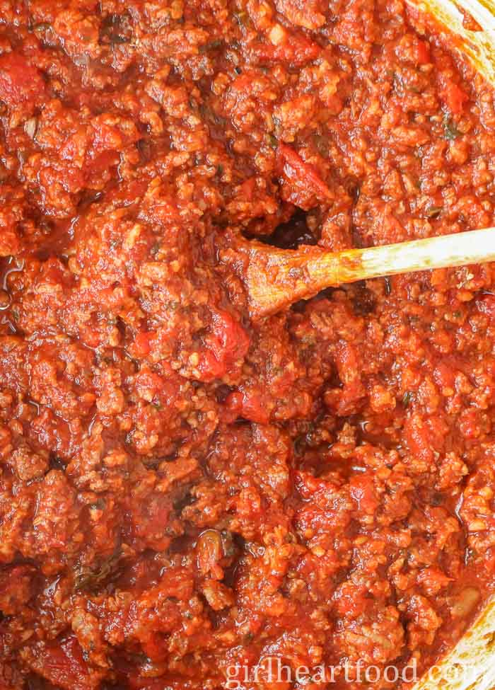 Meat sauce in a pot being stirred by a wooden spoon for a meat lasagna recipe.