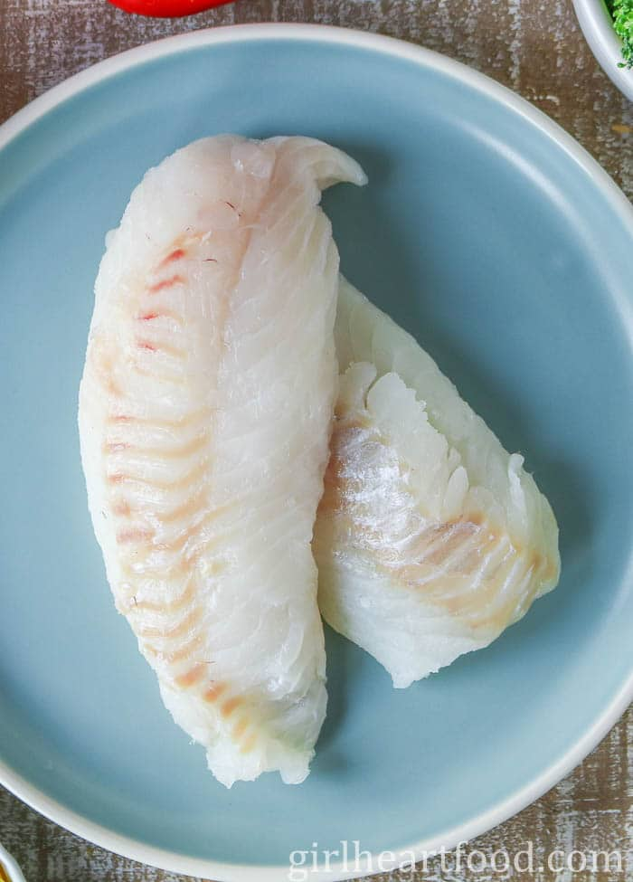 Raw cod fillets on a blue plate.