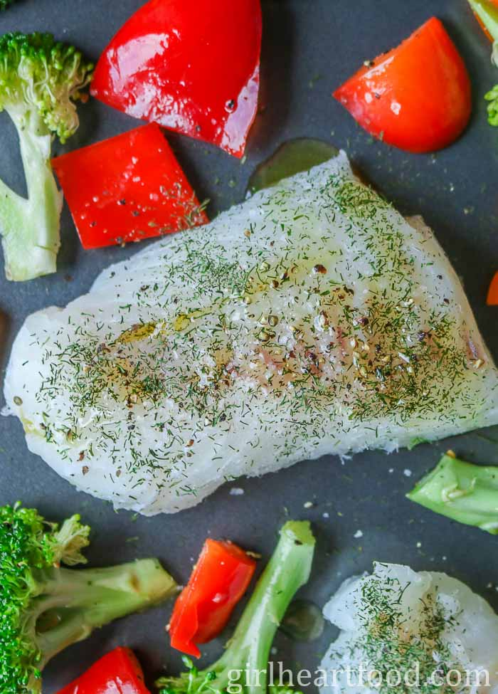 Cod fish sprinkled with salt, pepper, dill and olive oil next to vegetables on a sheet pan.