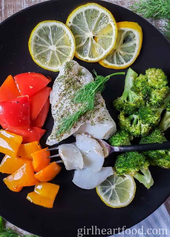 Cod with dill on a plate plate alongside vegetables and lemon slices.